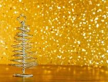 Metalliskt modernt julträd på den wood tabellen på guld- bakgrund för tonljusbokeh Arkivbild