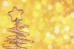 Metalliskt modernt julträd på guld- bakgrund för tonljusbokeh, xmas-ferie Fotografering för Bildbyråer