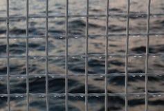 Metalliskt netto med droppar mot havsbakgrund Royaltyfri Foto