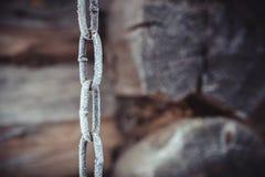 Metallkette bedeckt mit weißem Reif auf einem alten hölzernen Wandhintergrund stockfotos
