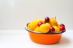 Metallkorb von Kirschbeeren und -aprikosen Stockbild