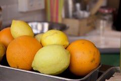Metallkorg med apelsiner och citroner Arkivbilder