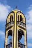 Metallkors på taket av en antik gul klockstapel Arkivfoto
