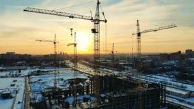Metallkräne errichten ein Haus auf einer Baustelle auf einem Sonnenunterganghintergrund stock video footage