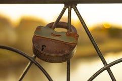 Metalll?set rusar kedjas fast till gallret av bron i heder av f?r?lskelse och lojalitet i inst?llningssolen arkivbilder