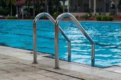 Metallleiter in der Poolnahaufnahme Stockbild