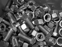 Metalllic nuts and bolts. Pile of metallic nuts and bolts in bin ready for use in construction royalty free stock photography