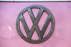 Metalllogo av Volkswagen på rosa bakgrund Det är logoen av den Volkswagen skåpbilen arkivbilder