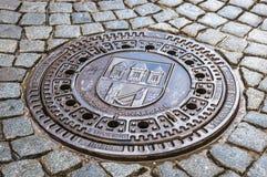 Metallluken-Abwasserkanaleinsteigeloch und Kopfsteinpflasterung Stockfotografie