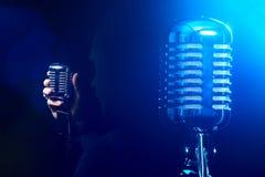 Metallmikrofon auf einem blauen Hintergrund Der Sänger singt ein Lied O Lizenzfreie Stockfotos