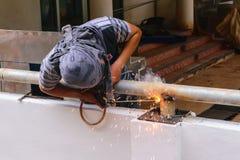 Metallo di collegamento della costruzione della saldatura elettrica di uso del lavoratore Fotografia Stock