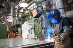 Metallo di saldatura del saldatore all'officina della fabbrica Immagini Stock