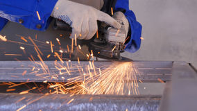 Metallo di sawing dell'artigiano con la smerigliatrice del disco in officina Metallo della macinazione con la volata delle scinti Fotografia Stock Libera da Diritti