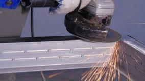Metallo di sawing dell'artigiano con la smerigliatrice del disco in officina Metallo della macinazione con la volata delle scinti Fotografia Stock