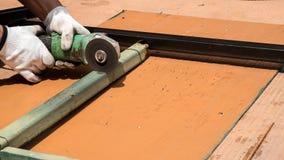 Metallo di taglio dell'operaio con la smerigliatrice Immagine Stock