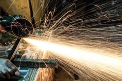 Metallo di taglio dell'operaio con la smerigliatrice Scintilla mentre frantumano il ferro fotografie stock libere da diritti