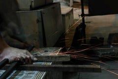 Metallo di taglio dell'operaio con la smerigliatrice Scintilla mentre frantumano il ferro fotografie stock