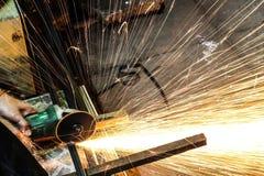 Metallo di taglio dell'operaio con la smerigliatrice Scintilla mentre frantumano il ferro fotografia stock libera da diritti