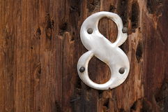 Metallo numero 8 su priorità bassa di legno Fotografie Stock