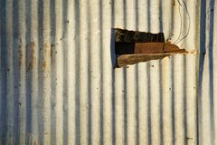 Metallo ondulato con un foro fotografie stock libere da diritti