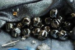 Metallpärlor med skrapor på textilen Royaltyfri Foto