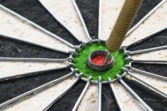 Metallpilar har slågit den röda bullseyen på ett pilbräde framförd modig bild för pilar 3d Pilpil i målmittpilarna i slut för öga Royaltyfri Bild