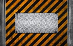 Metallplatte auf schwarzem gelbem Vorsichtmuster Stockfotos