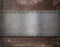 Metallplatte mit Nieten über rustikalem Stahl Lizenzfreie Stockbilder