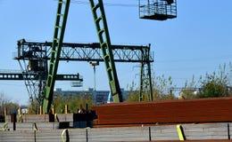 Metallprodukter, metall, på bakgrunden av en lastningsbryggakran på en industriell plats royaltyfri fotografi