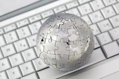 Metallpuzzlespielkugel auf Tastatur Lizenzfreie Stockfotografie