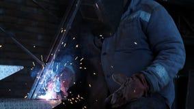 Metallschweißende Nahaufnahme Männlicher Schweißer, der in der Schutzmaske auf Eisentreppe arbeitet Industrielles Aufbau-Konzept  stock footage