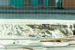 Metallsicherheitszaun auf der Straße parallel zum Graben voll vom Sand nach Straße exscavation Arbeit Stockfotografie