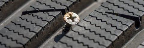 Metallskruv i skadat däck Royaltyfri Bild