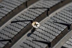 Metallskruv i skadat däck Royaltyfri Foto
