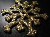 Metallsnöflinga med guld- paljetter på svart bakgrund Den guld- snöflingan med blänker och skimrar Jul dekorativ beståndsdel, lek royaltyfri foto