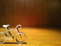 Metallspielzeug-Zweiradfahrrad auf hölzernem Hintergrund Stockbild