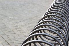 Metallspiral av den tomma cykelställningen på en trottoar Royaltyfri Foto