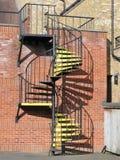 Metallspiraltrappuppgång med gula moment arkivfoto
