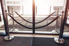 Metallställningsbarrikad med sammetrepet framme av glass dörrar Stängd ingång till köpcentret arkivfoton