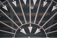 Metallstaket som dekoreras med skarpa pilar in i den runda formen, brun stålpil Arkivbilder