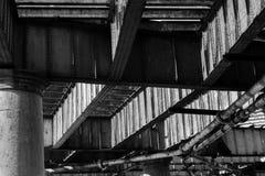 Metallstrålar och konkreta kolonner av flodpirundersidan Arkivfoto