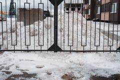 Metallsvartstaket I vinter driver snö i parkeringsområdet Nästan hem Arkivfoto