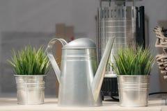 Metalltekanna och dekorativa metallhinkar med växter för garnering av ett kafé på gatan royaltyfri bild