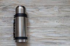 Metallthermosflasche auf einem woden Hintergrund Beschneidungspfad eingeschlossen Lizenzfreie Stockfotografie