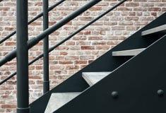 Metalltrappuppgång mot en tegelstenvägg Arkivfoto