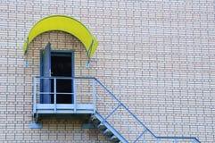 Metalltreppenhaus und eine offene Tür auf einer Backsteinmauer des Hauses stockfotografie