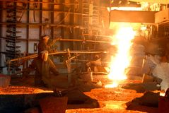 Metallugry. Glowing, molten hot steel. Stell casting Stock Images