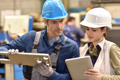 Metallurgic workers checking on production Stock Images