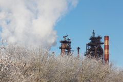 Metallurgical plant with cloud of pollution exhaust with frozen winter bush in foreground at daylight.  royalty free stock photography