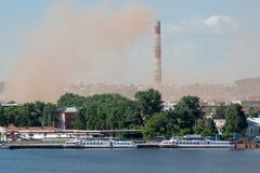 Metallurgical plant near a beautiful lake. Emission of nitrogen oxide into the atmosphere. Pollution of the environment. Red smoke Stock Photo